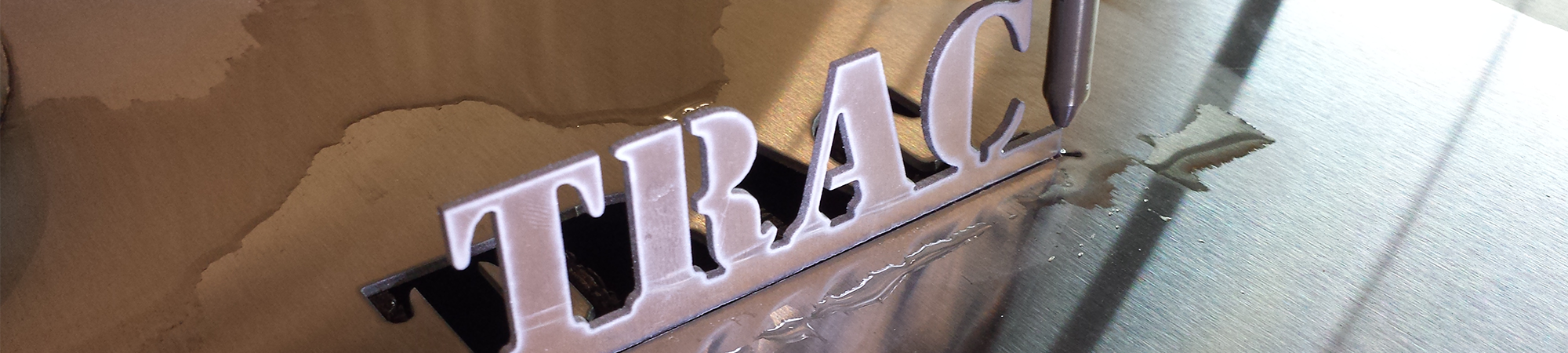 Trac Precision name freshly cut from metal on the water jet.